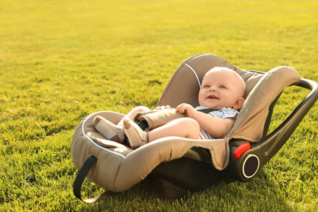 zlaté dieťa v detskej autosedačke na zelenej tráve